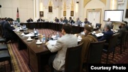 Afghan President Ashraf Ghani (next to flag) briefed members of his largely unfilled cabinet in Kabul on April 15.