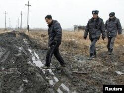 Российские полицейские ведут нелегального китайского трудового мигранта, обнаруженного во время рейда на ферме. Красноярский край, 7 апреля 2011 года.