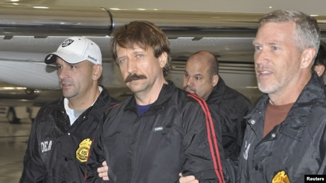 Convicted Russian arms dealer Viktor Bout (center) is escorted by U.S. Drug Enforcement Administration officers after arriving in the United States following his extradition from Thailand last year.