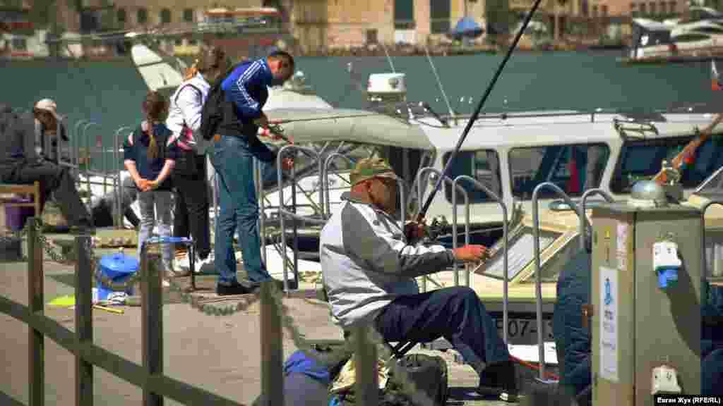 С12 мая разрешена рыбалка, поэтому рыбаки удят рыбу в Балаклавской бухте