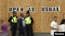 Patrulă de poliţie în faţa vitrinei sparte a unui magazin