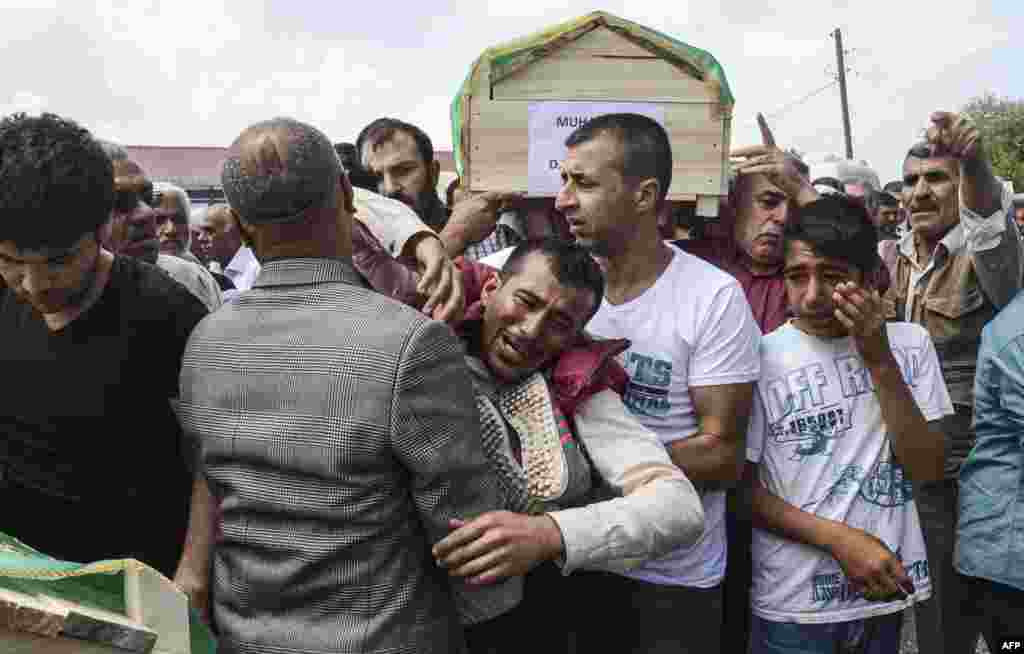 Kurdish mourners cry as they carry coffins on the outskirts of the majority Kurdish city of Diyarbakir, Turkey, after a massive explosion hit the area. The blast was caused after a huge quantity of explosives hoarded by Kurdish rebels blew up accidentally. (AFP/Ilyas Akengin)