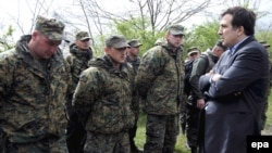 Georgian President Mikheil Saakashvili (right) talks with soldiers who took part in a mutiny at the Mukhrovani base last year. The opposition claims the mutiny was a distraction planned by the government.