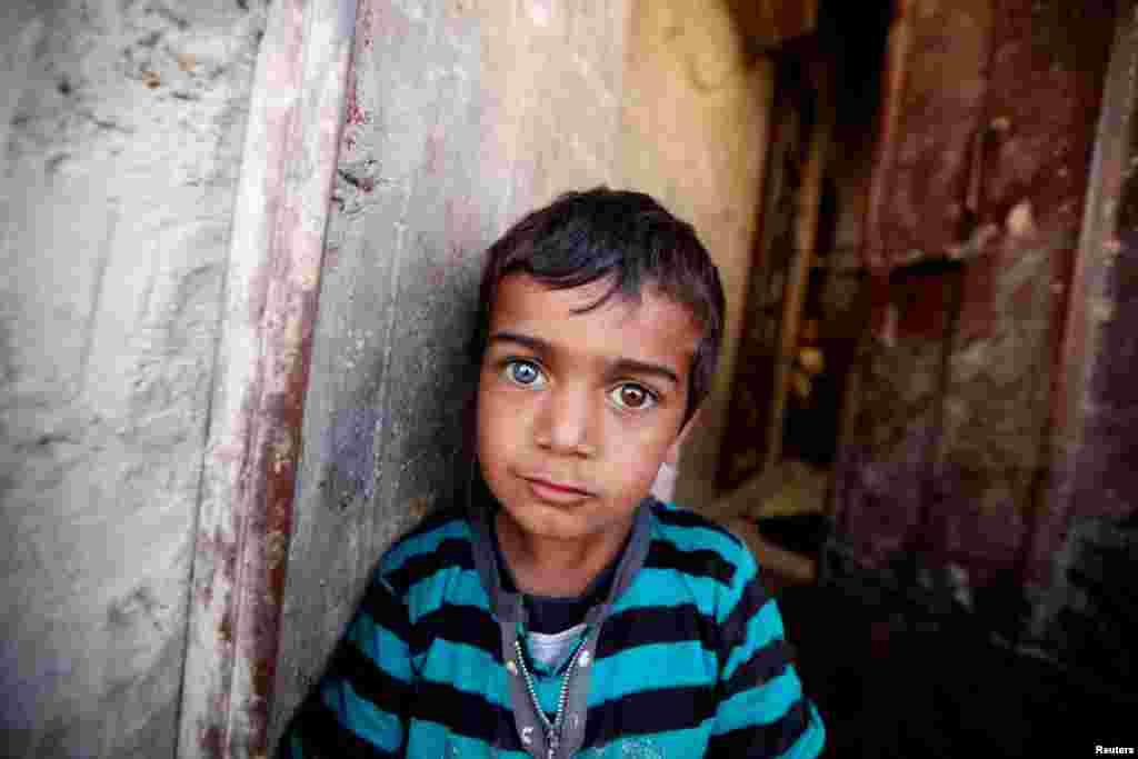 Një djalë me sy të ngjyrave të ndryshme, pret te porta e shtëpisë së familjes së tij gjatë fushatës së vaksinimit shtëpi më shtëpi, kundër poliomelitit në kryeqytetin e Jemenit, Sanaa.