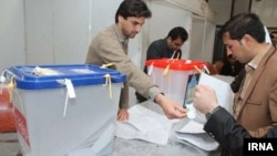 Workers begin processing votes at an election center in Tehran.