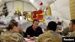 British Prime Minister David Cameron (center) eats breakfast with British forces at Camp Bastion in Helmand Province in December.