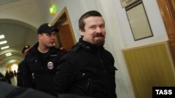 Opposition activist Leonid Razvozzhayev is escorted by a Russian police guard to his September 30 appearance in the Basman District Court.