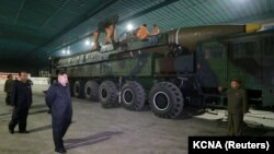 """Солтүстік Корея басшысы Ким Чен Ын (сол жақта) әскерилермен бірге """"Хвасон-14"""" құрлықаралық баллистикалық зымыранын қарап жүр. 5 шілде 2017 жыл."""