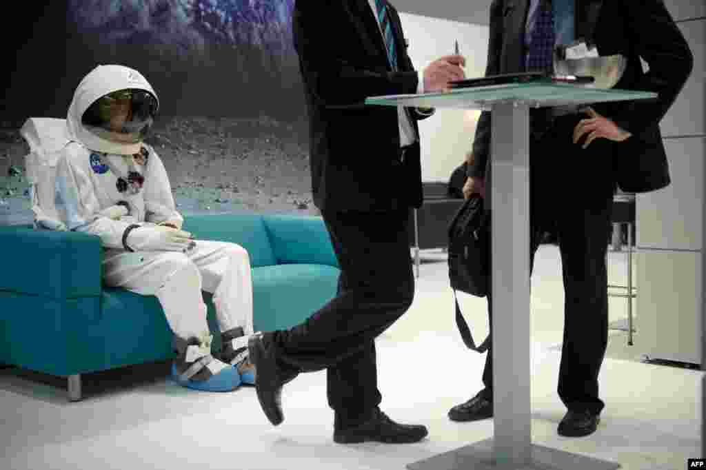 A man in a spacesuit is seen sitting on a couch behind two businessmen at the Wittenstein booth at the Hannover industrial fair in Hannover, Germany. The fair presents a cross-section of key industrial technologies. (AFP/Odd Andersen)