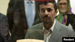 Iranian President Mahmud Ahmadinejad examines the Cyrus Cylinder at the National Museum in Tehran.
