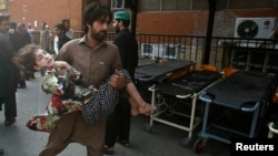 A man carries a young girl who was injured in the October 7 bomb blast near Peshawar that appeared to target police providing security for a polio-eradication effort.