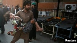 Bir adam bomba partlamasynda ejir çeken gyzjagazy keselhana göterip barýar. Peşawar, Pakistan. 7-nji oktýabr, 2013 ý.