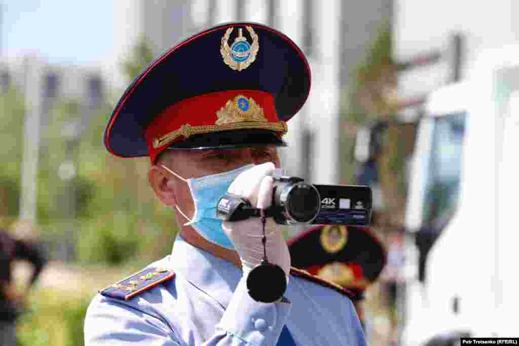 A police officer shoots video at the site of a planned protest rally in Nur-Sultan.