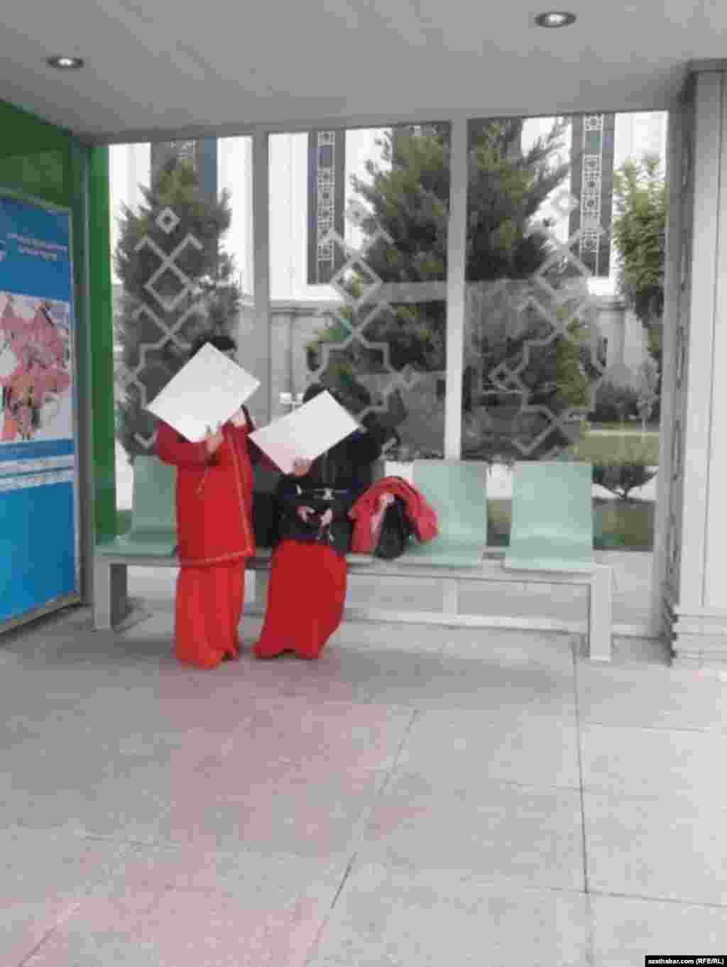 Девушки в традиционных платьях туркменских студенток на автобусной остановке в Ашхабаде