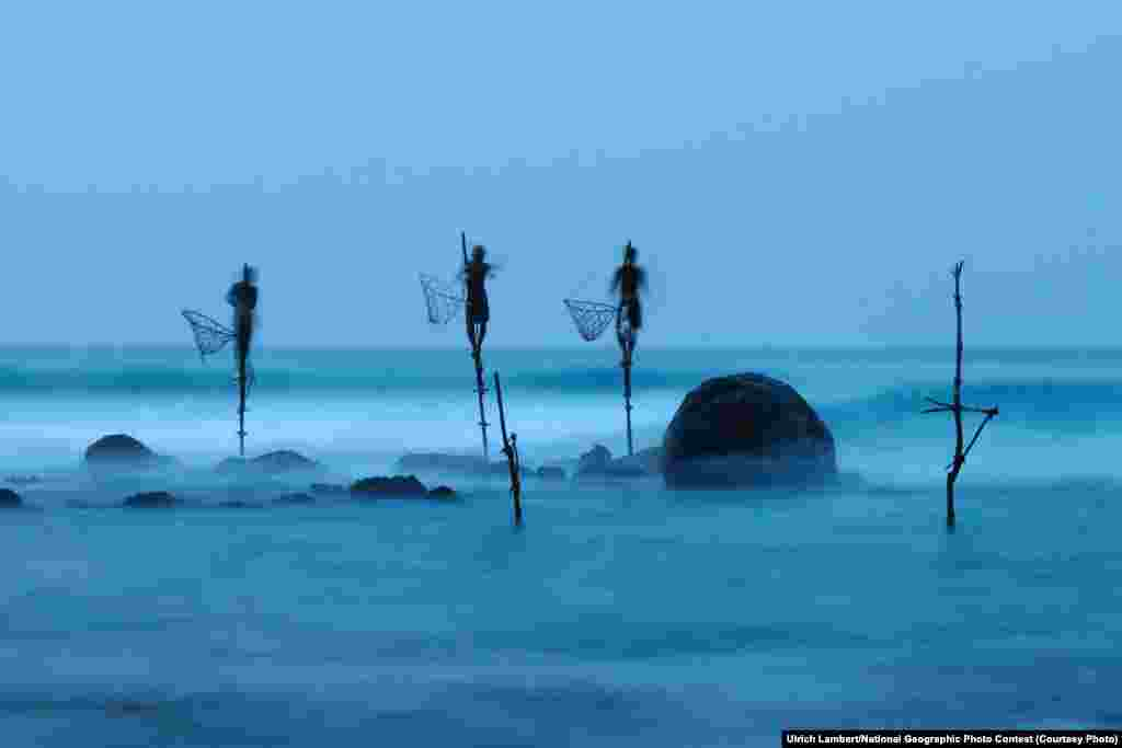 HONORABLE MENTION: Stilt Fishing (Midigama, Sri Lanka) -- Stilt fishing is a typical fishing technique only seen in Sri Lanka. The fishermen sit on a cross bar called a petta tied to a vertical pole planted into the coral reef. This long exposure shot shows how unstable their position is. (Caption by photographer Ulrich Lambert)