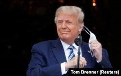 Президент США Дональд Трамп, выходя на балкон Белого дома, снимает маску перед своим выступлением