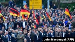 Demonstrators wave German flags during a protest organized by the right-wing populist Pro Chemnitz movement, the far-right Alternative for Germany (AfD) party, and the anti-Islam Pegida movement on September 1 in Chemnitz.