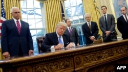 U.S. President Donald Trump signs an executive order on January 23.