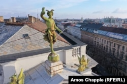 A statue of Hermes looks into the camera from his perch atop the Fonciere Palace, built in 1882 to house an insurance company.