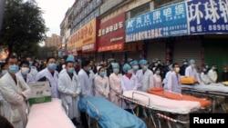 Медицинский персонал ожидает с носилками рядом с местом пожара в одном из торговых центров в провинции Гуандун, 5 февраля 2015 года.