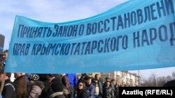 Қырым татарларының құқығын қалпына келтіру туралы талап айтылған жазу ұстап тұрғандар. Симферополь, 23 ақпан 2014 жыл. (Көрнекі сурет)