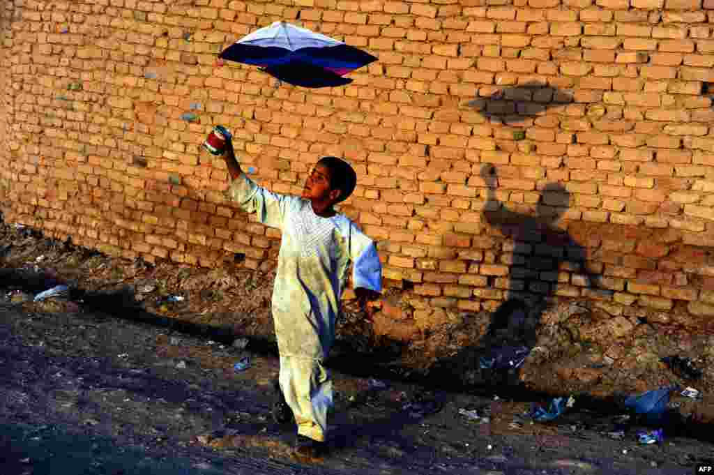 An Afghan child plays with a kite on the outskirts of Herat onOctober 20. (AFP/Aref Karimi)