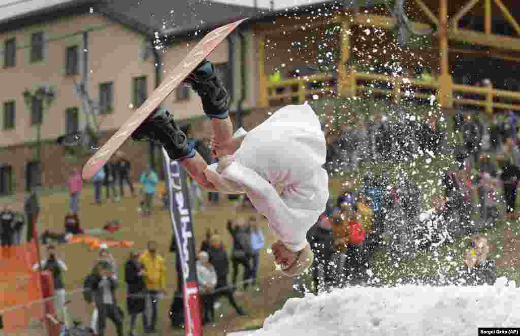 A Belarusian snowboarder takes part in a competition at an entertainment center in the town of Logoisk, 40 kilometers north of Minsk. (AP/Sergei Grits)