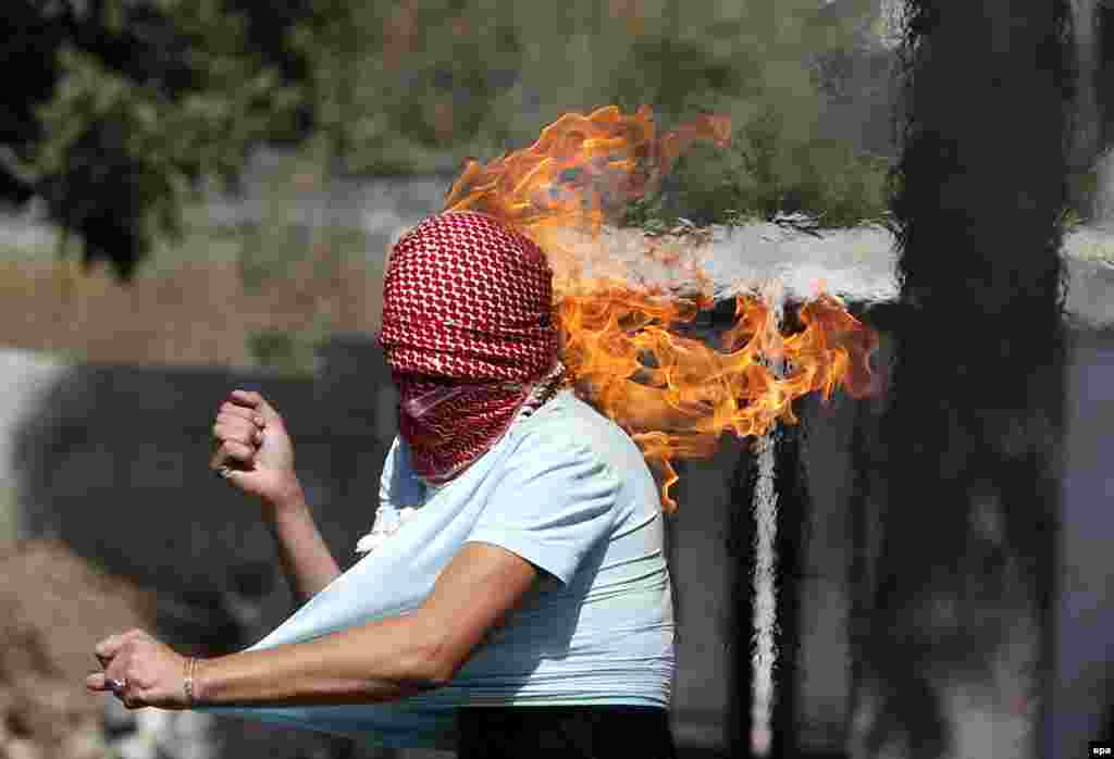 A Palestinian protester sets fire to himself as he throws a Molotov cocktail during clashes with members of the Israeli armed forces in the West Bank city of Hebron. The past two weeks have seen the worst spell of street violence in Israel and the Palestinian areas in years, stirred in part by Muslim anger over perceived changes to the status quo observed at a disputed Jerusalem holy site. (epa/Abed Al Hashlamoun)
