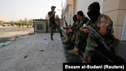 Iraqi security forces stand guard near government buildings in Basra on September 5.