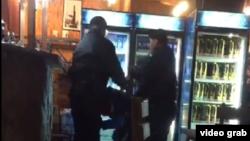 Күзетшілердің кафеге калген масаң адамдарды соққыға жықты делінген видеосынан скриншот.