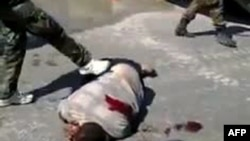 A Youtube video grab shows what antiregime activists in Syria say are pro-government militia members dressed as soldiers kicking the corpse of a man in the city of Homs on September 5.
