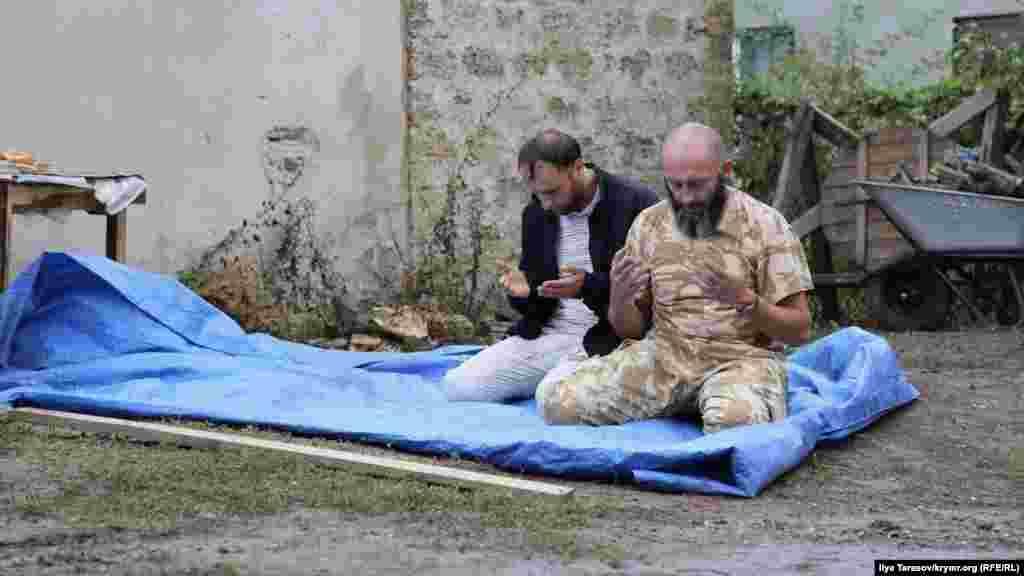 Активісти Руслан Сулейманов і Різа Ізетов читають намаз у дворі. Останній, зустрічаючи Мустафаєва біля спецприймальника, пожартував, що той «абсолютний рекордсмен з відсиджених діб за адмінарешти»