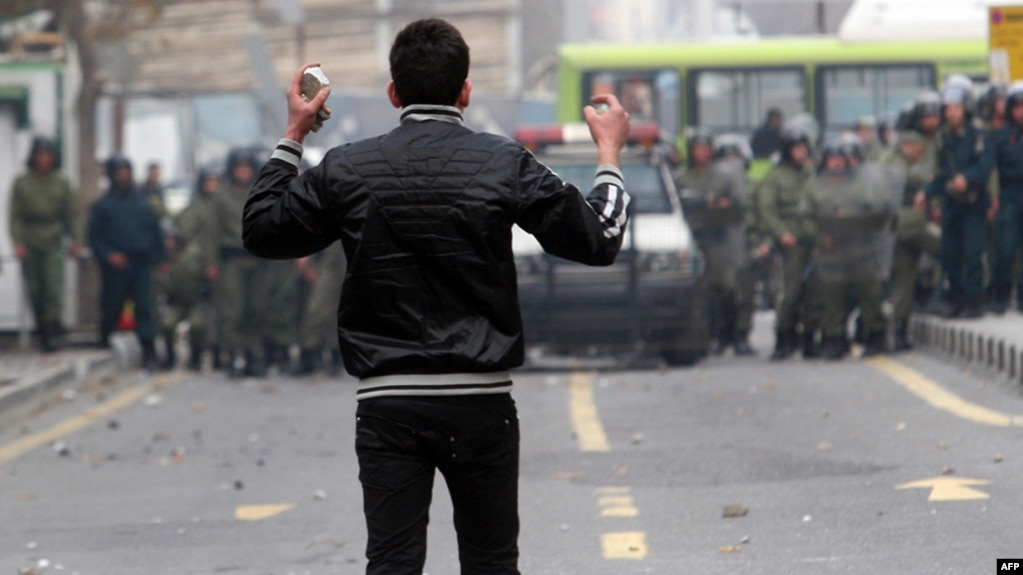An Iranian opposition protester faces security forces during clashes in Tehran in December 2009, following the reelection of Mahmud Ahmadinejad as president.