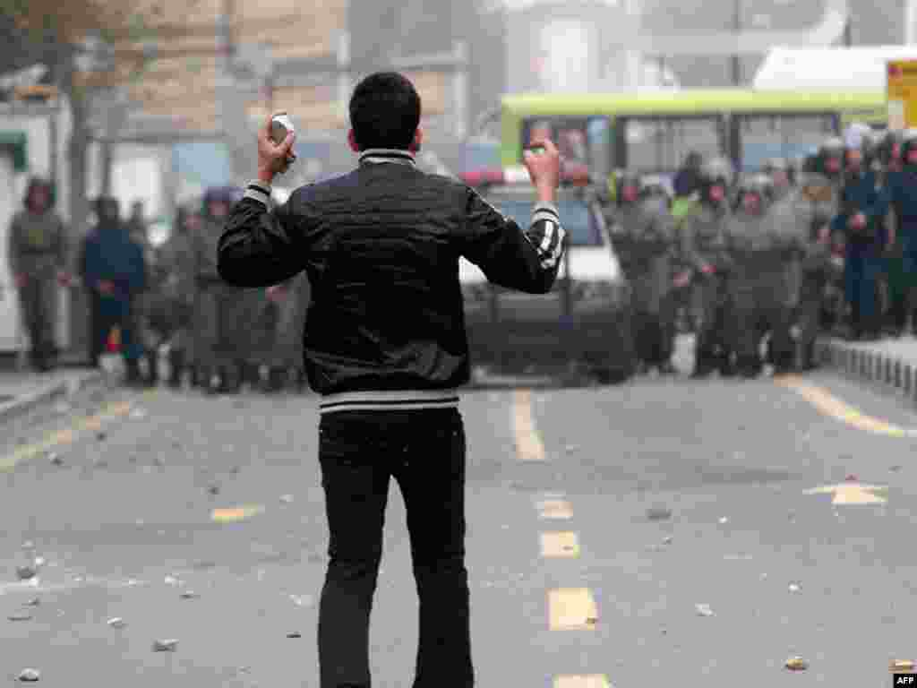 An opposition protester holds stones as he faces security forces. (AFP)