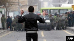 Iran -- An Iranian opposition protester holds stones as he stands opposite security forces during clashes in Tehran on December 27, 2009.