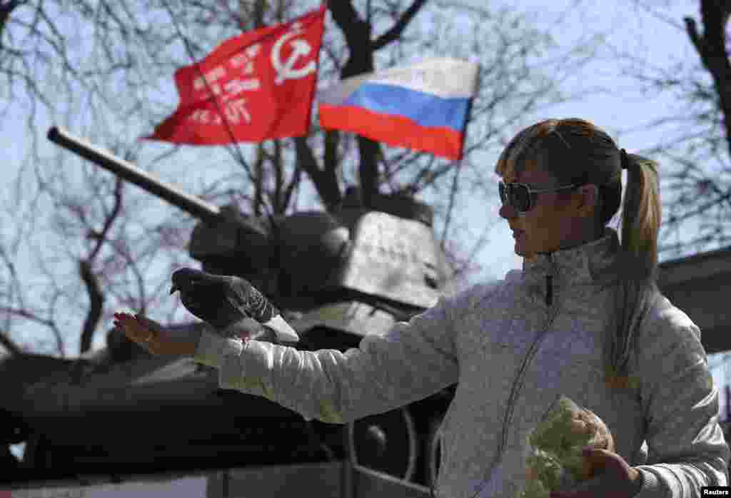 Қырымда референдум өтетін күннің қарсаңында кептер ұстап тұрған әйел. Симферополь, Украина, 15 наурыз 2014 жыл.