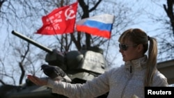 A woman feeds a pigeon near a monument displaying a Soviet-era tank as well as a Russian flag in the Crimean capital Simferopol on March 15.