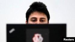 یکی از هکرهای رومانی در حال کار بر روی لپتاپ خود در دفترش در بخارست