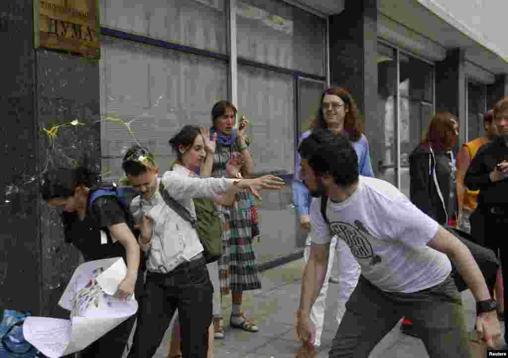 An Orthodox believer throws an egg at gay-rights activists outside the State Duma.