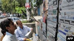 Pakistanis in Islamabad read newspapers the day after Pervez Musharraf's resignation on August 18, 2008.