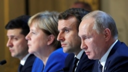 Ukraine's Volodymyr Zelenskiy, (left to right) Germany's Angela Merkel, France's Emmanuel Macron, and Russia's Vladimir Putin attend a press conference after a summit on Ukraine at the Elysee Palace in Paris on December 9.