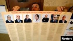 Президенттікке кандидаттар суреті салынған плакатты ұстап тұрған адам. Ереван, 17 ақпан 2013 жыл.