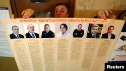 Сайлау комиссиясының өкілі президенттікке үміткерлердің суреттерін ұстап тұр. Ереван, 17 ақпан 2013 жыл.