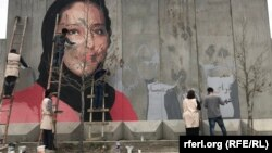 The mural in Kabul of slain human rights activist Hamida Barmaki as it was being painted.
