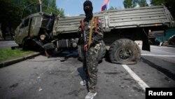 Пророссийский сепаратист стоит рядом с подорванным грузовиком у донецкого аэропорта. 29 мая 2014 года.
