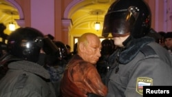 Police detain a man wearing a Vladimir Putin mask during an opposition protest in St. Petersburg.