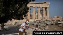 Посетители моют руки перед Парфеноном, памятником античной архитектуры, расположенным на афинском Акрополе. 18 мая 2020 года.