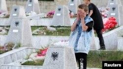 Një djalë duke u lutur para varrezave në Reçak.