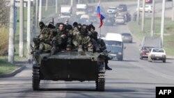 Украинанын Краматорск шаарындагы Орусиянын желеги сайылган аскердик техникадагы курал көтөргөн адамдар. 16-апрель, 2014-жыл.