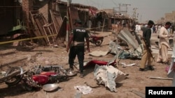 Pakistani police and security officials collect evidence at the site of a bomb blast in Dera Allah Yar, in Balochistan Province, on March 22.